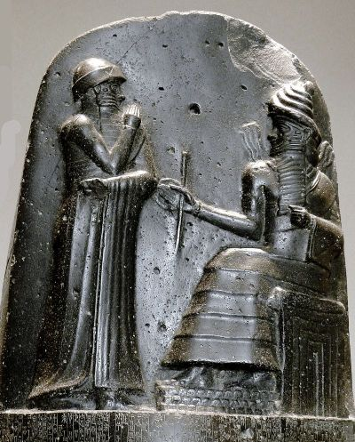 Hammurabi (standing) receiving his royal insignia from Shamash [image from Wikimedia Commons].