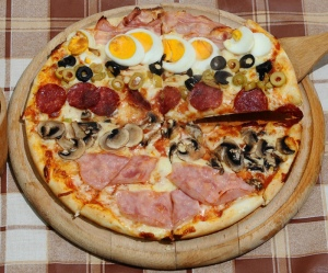 A pizza with various toppings. Image: Pizza Masetti Craiova, Romania (Flickr)  [CC BY 2.0 (http://creativecommons.org/licenses/by/2.0)], via Wikimedia Commons.